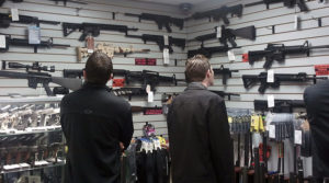 Customers view semi automatic guns on display at a gun shop in Los Angeles California