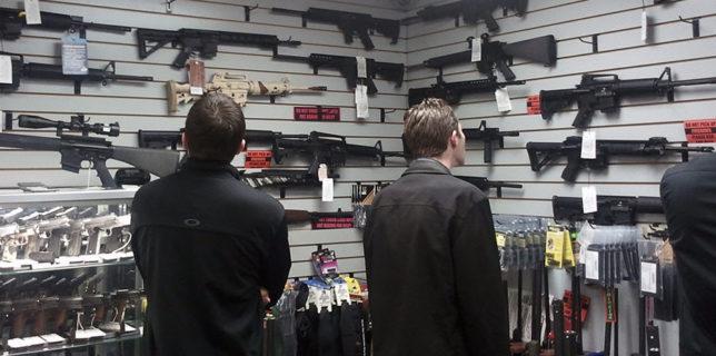 Customers view semi automatic guns on display at a gun shop in Los Angeles California